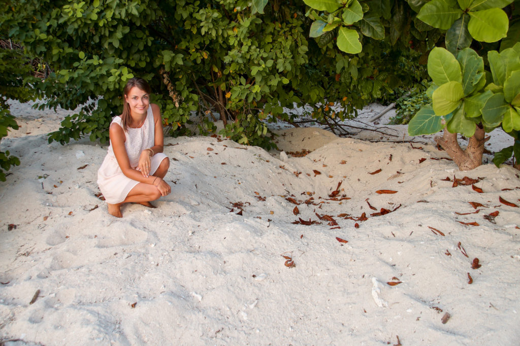 a girl sitting on the sand next to the turtle hole