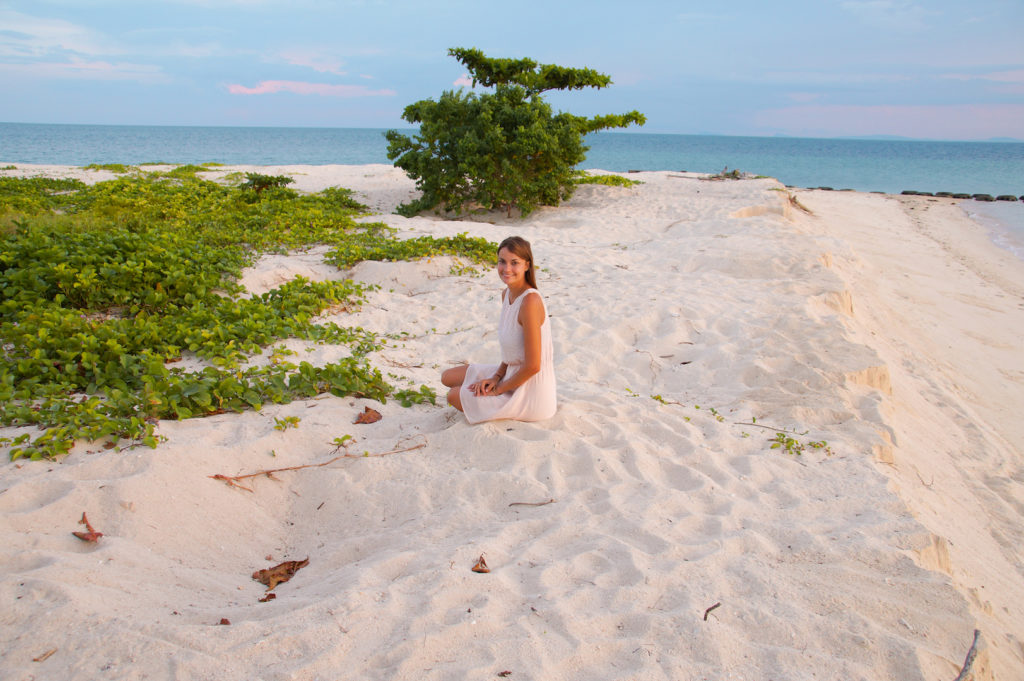 a girl sitting on the white sand with the ocean view