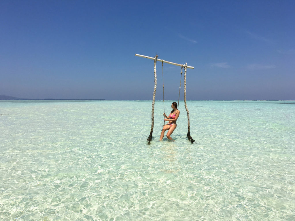 woman in a swimwear sitting on the swing in the blue water in Karimunjawa islands, Indonesia