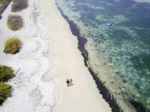 drone shot of 2 adults walking on a beach on Gili Air which has some of the best beaches in southeast asia