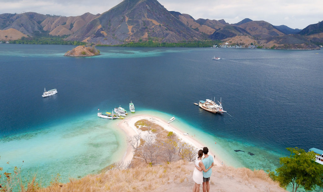 a drone shot of 2 people standing on top of kelor island enjoying the view on the surrounding islands and the ocean