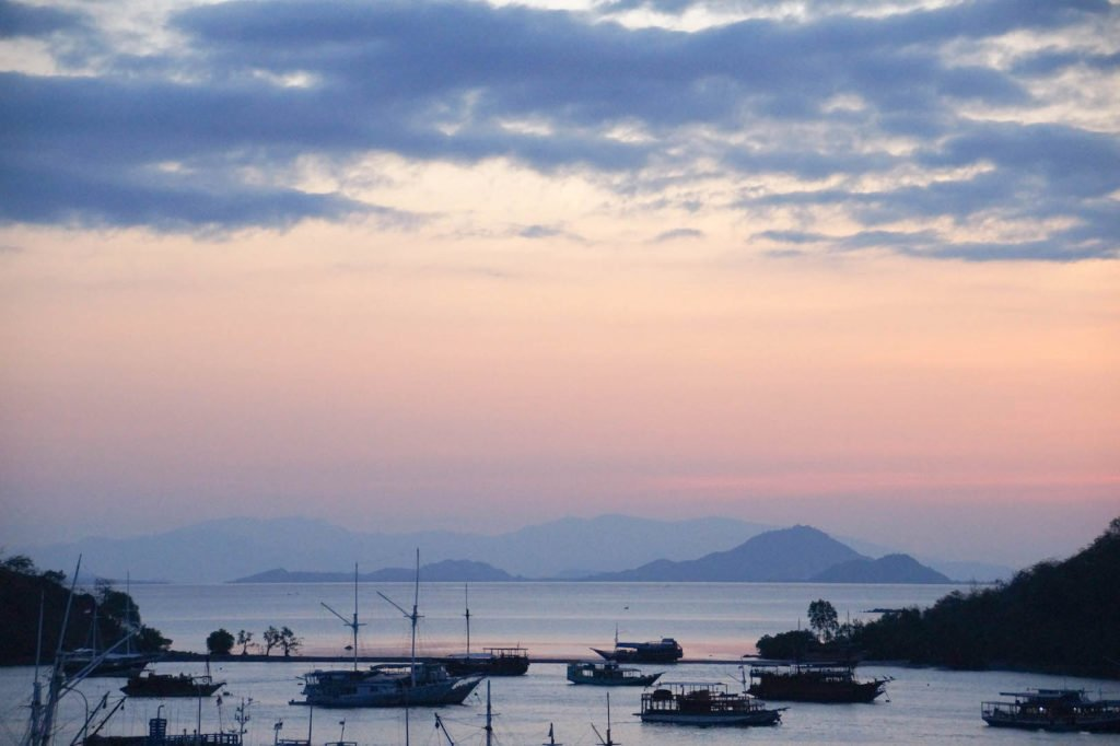view on a Labuan Bajo harbor during sunset with several boats around