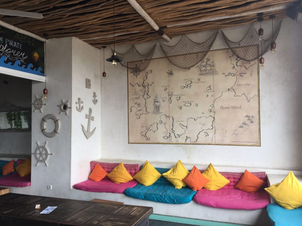a table and a bench with coloful pillows and a map above on a wall