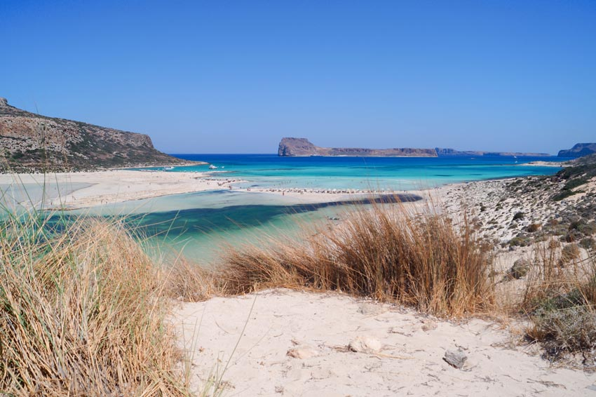view from a sand dune on balos bay in crete with blue water
