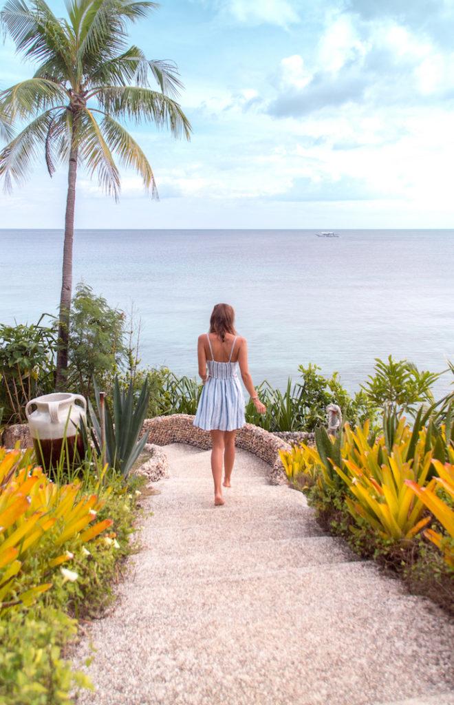 Girl walking down steps toward the ocean. Bohol itinerary