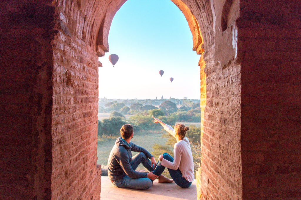 two people sitting on the ground and looking at the ballon in Bagan, Myanmar