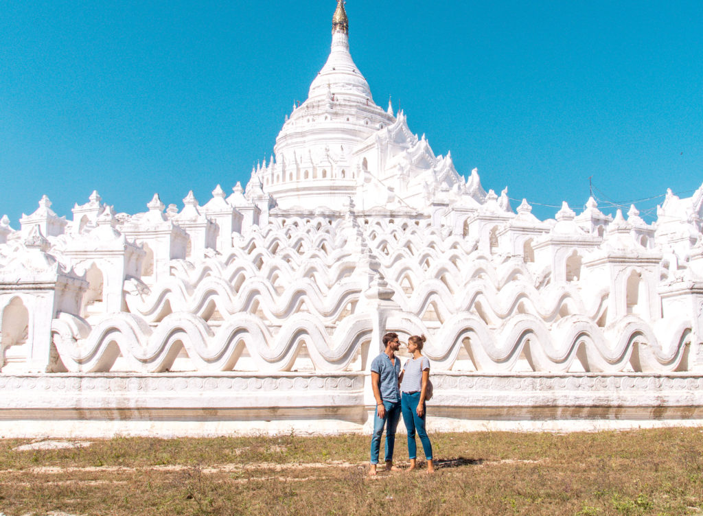 two people standing in front of the white temple in Mandalay