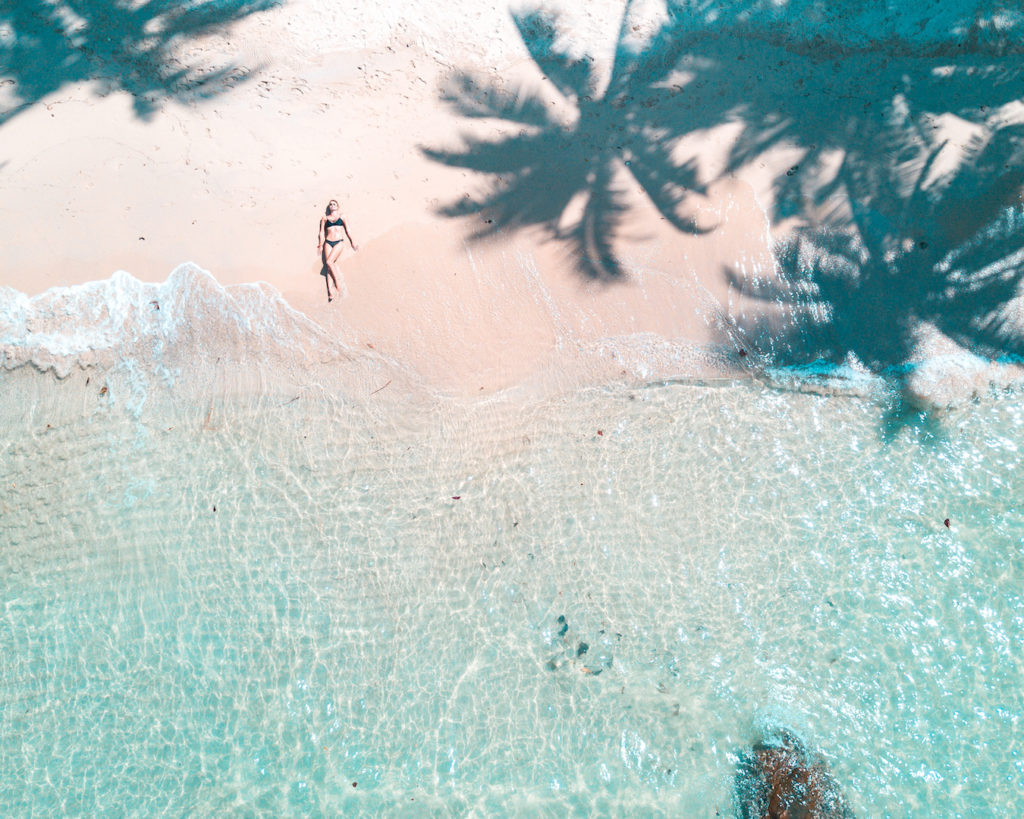 arial shot on the palm trees, woman lying on the beach and blue water on Koh Kood, Thailand
