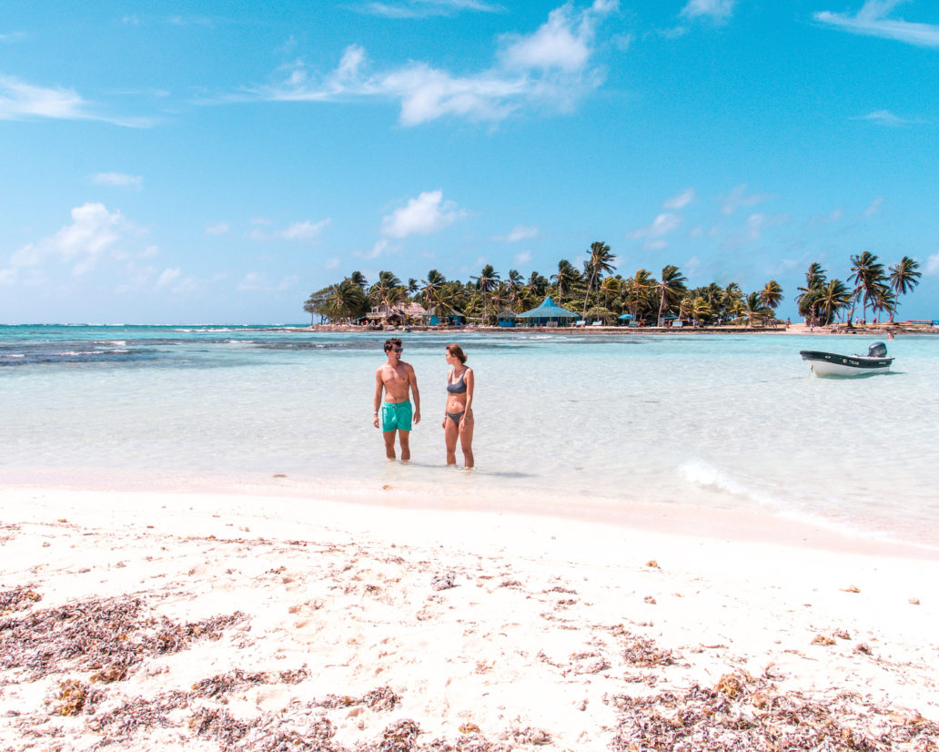 2 adults in swim wear stand in shallow waters with a boat and a small island covered by palm trees and a few huts in the background
