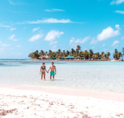 two people holding hands on white sand beach with perfect azure water on San Andres which is one of the most beautiful places in South America
