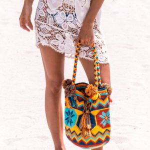 a woman wearing a white dress and holding colourful Handmade Wayuu Bag
