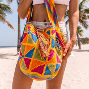 a woman wearing Authentic Handmade Colombian Wayuu Mochila Bags in orange and yellow colours