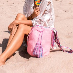girl in a white dress holding a lollipop and pink Authentic Handmade Wayuu Bag