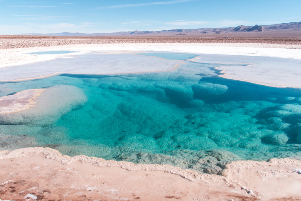 a view on a small lake with a blue water and white salt around
