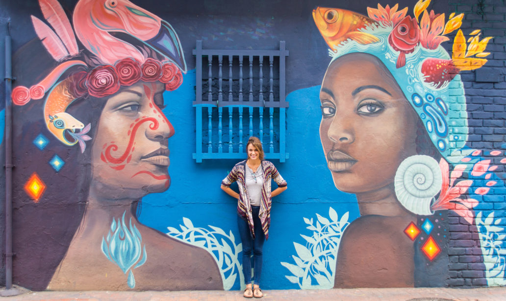 a pretty girl posing in front of a mural displaying two women in Bogota, Colombia