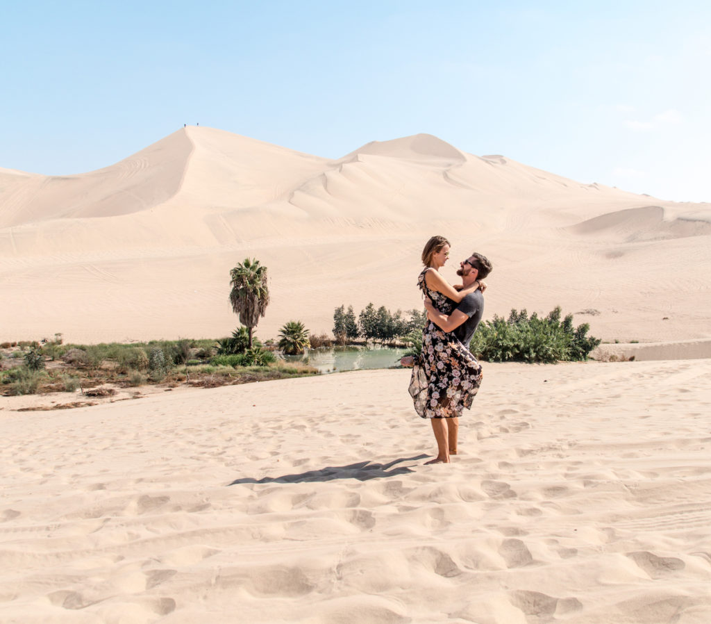 a couple hugging each other in the middl of the desert and sand with an oasis in the background
