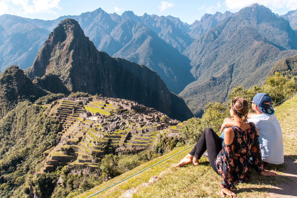 two people sitting on the green grass in front of the Machu Picchu mountain