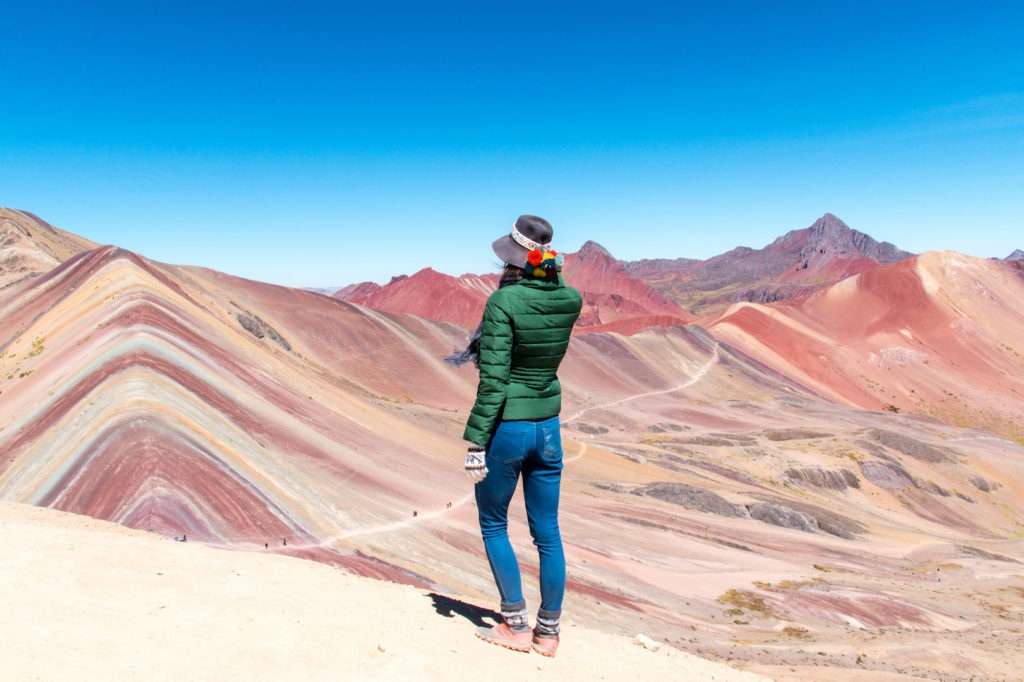 a woman standing on the red hill with a green hat in Rainbow mountain which is one of the most beautiful places in South America