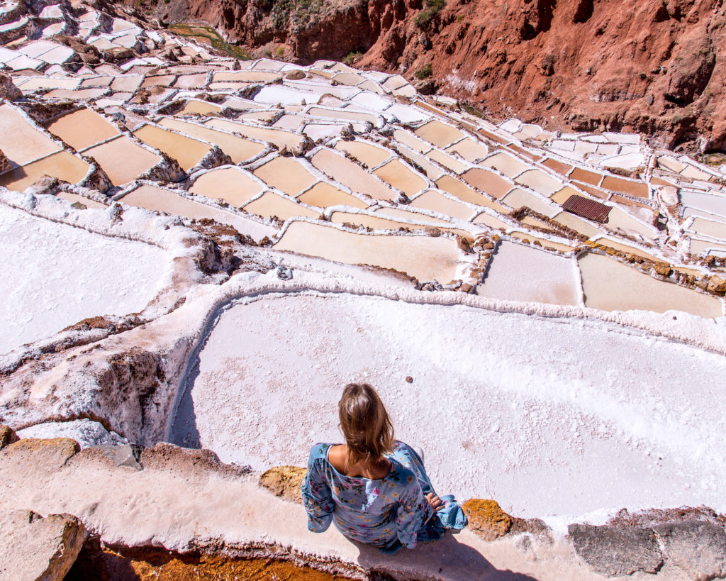 a woman in a blue dress standing in front of the pink salt mines in Salinas de Maras in Peru