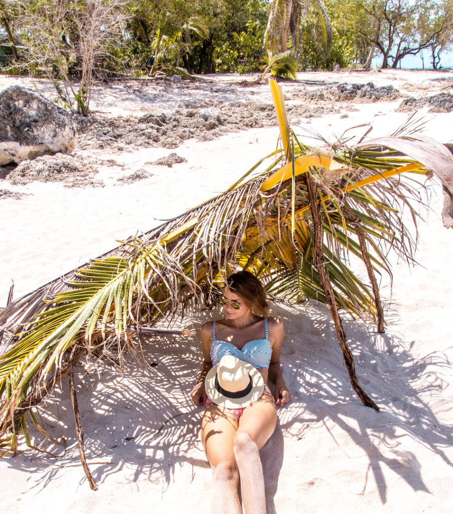 a girl sitting on the white sand with a palm tree above her head