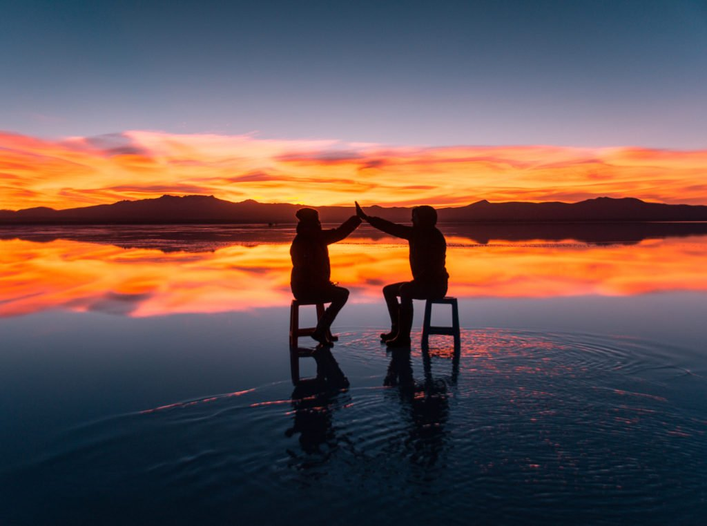 two people sitting on the chairs and watching sunrise with orange colours and mountains in the background at salt flats in Bolivia