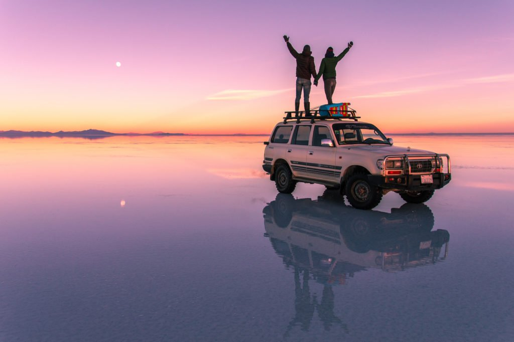 two people standing on the car and looking at the pink sunset colours in Salar de Uyuni, dreamy bucket list destinations