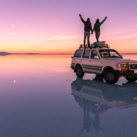 two people standing on the car and looking at the pink sunset colours in Salar de Uyuni.
