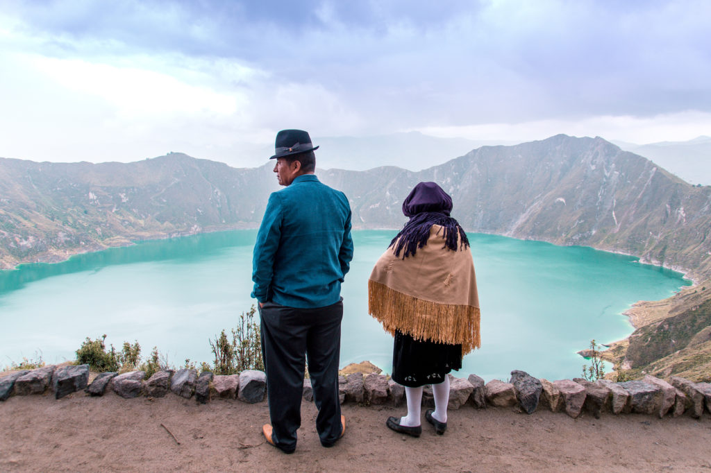 two people, men and woman standing in front of the blue lake wearing traditional Peruvian costumes