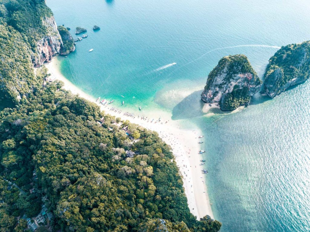 a drone photo of Ao Phra Nang Beach with forest and several big rocks in the water