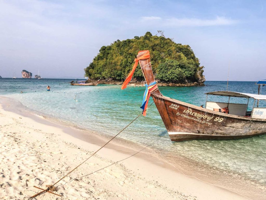 a thai boat anchored on a beach in front of a tiny island that is covered by trees