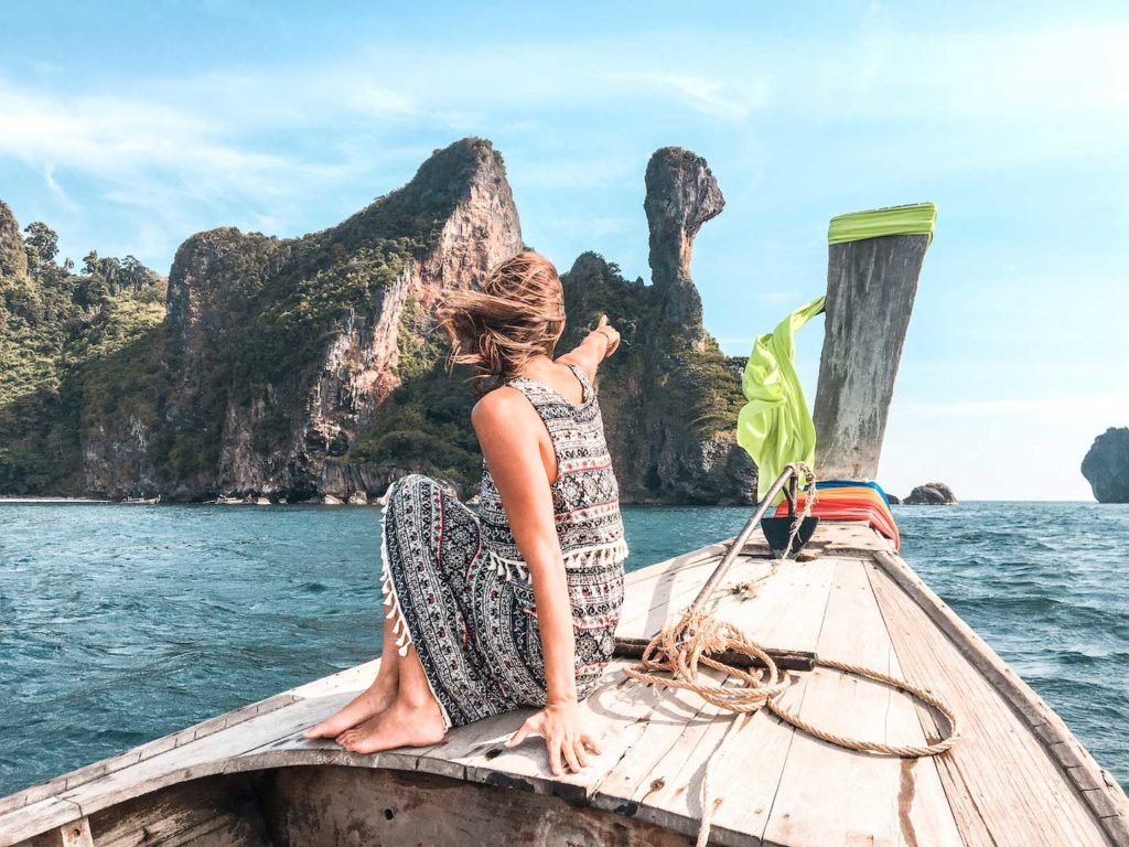a girl sitting on a thai boat and pointing at the rocky mountain
