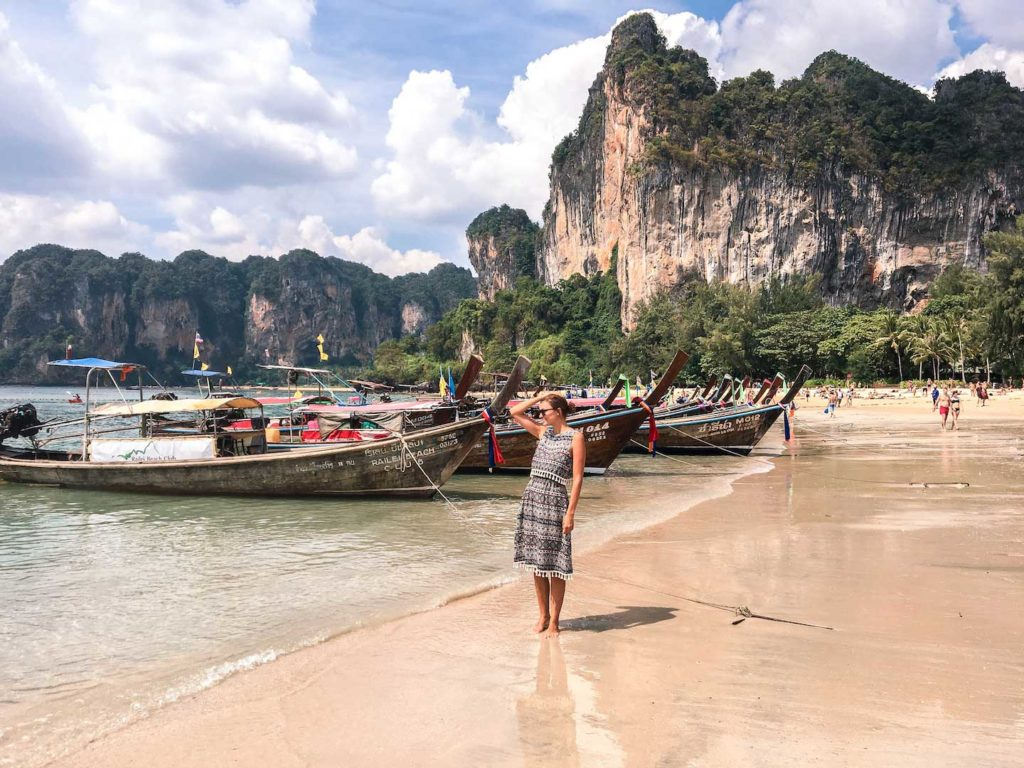 a girl standing on Railay beach with several Thai boats and karst rocks in the background, one of the best experiences in Thailand, Railay Beach
