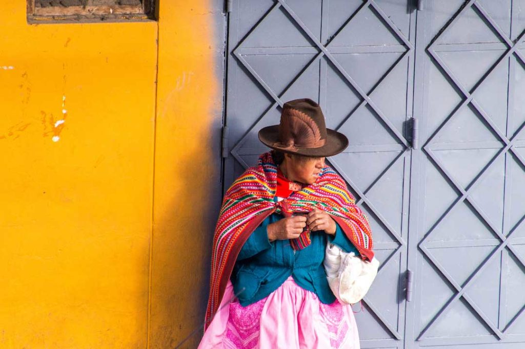 peruvian lady in traditional outfit standing in front of the yellow and grey wall in Huaraz, Peru