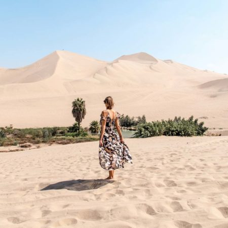 woman in a dress in Huacachina desert with oasis