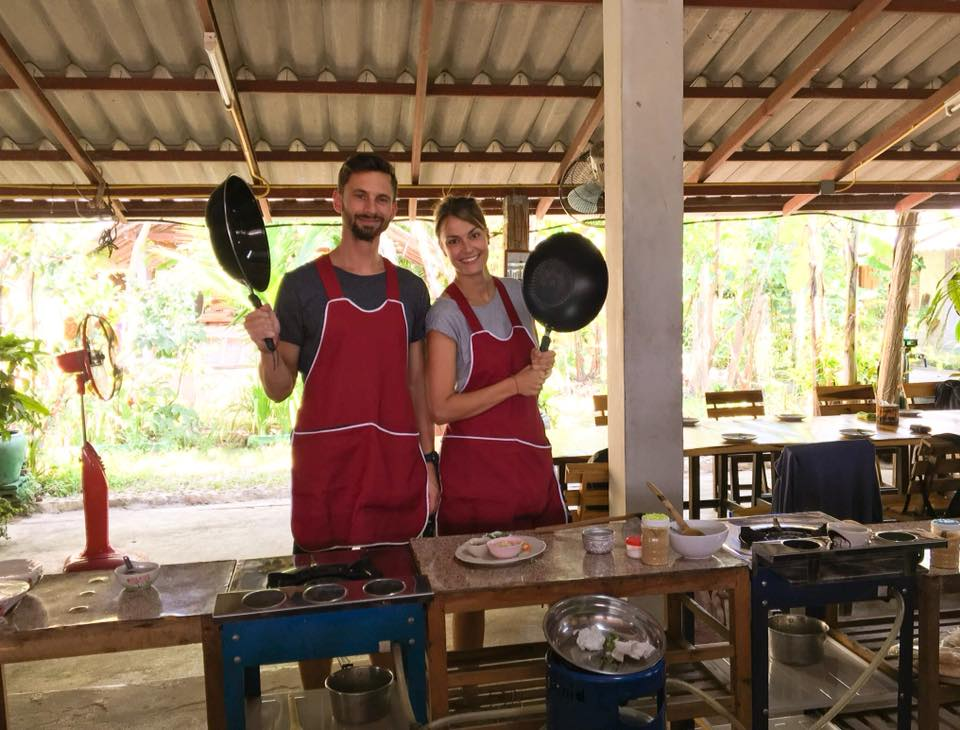 2 people holdings pans participating in a Thai cooking class which is a must do activity for your 10 day thailand itinerary