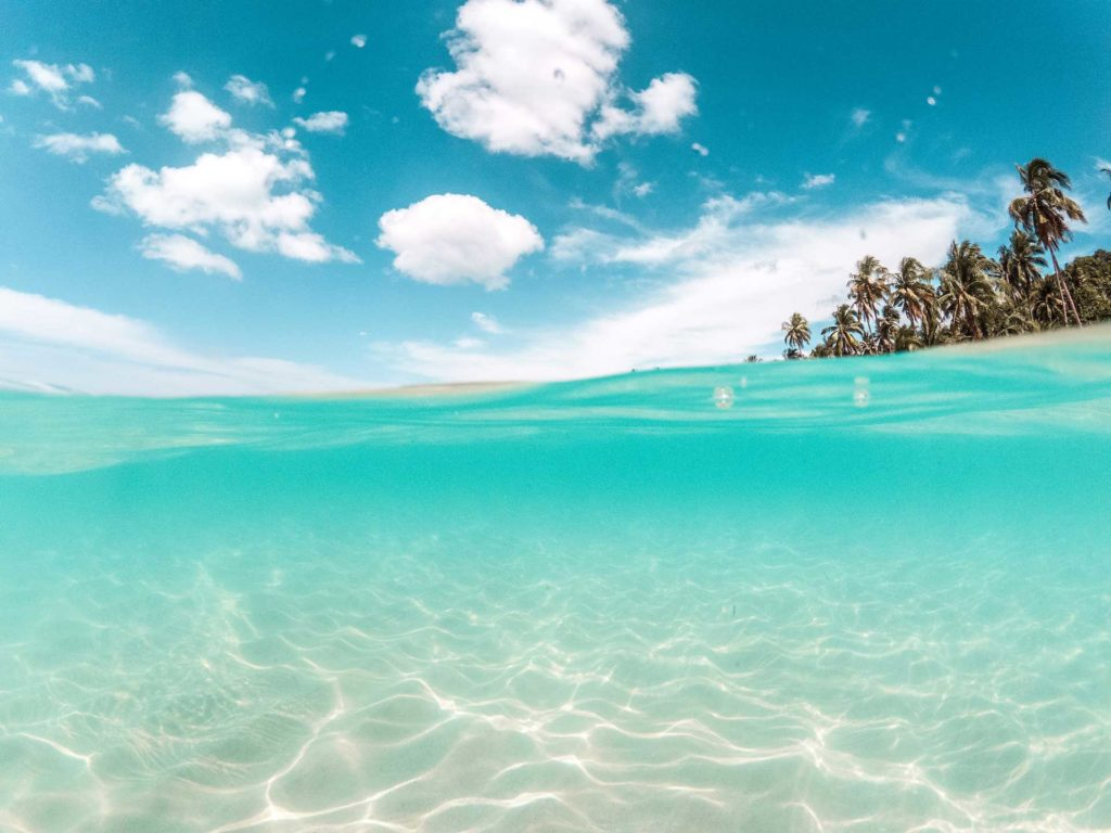 an underwater picture with white sand on the ocean floor and blue water above