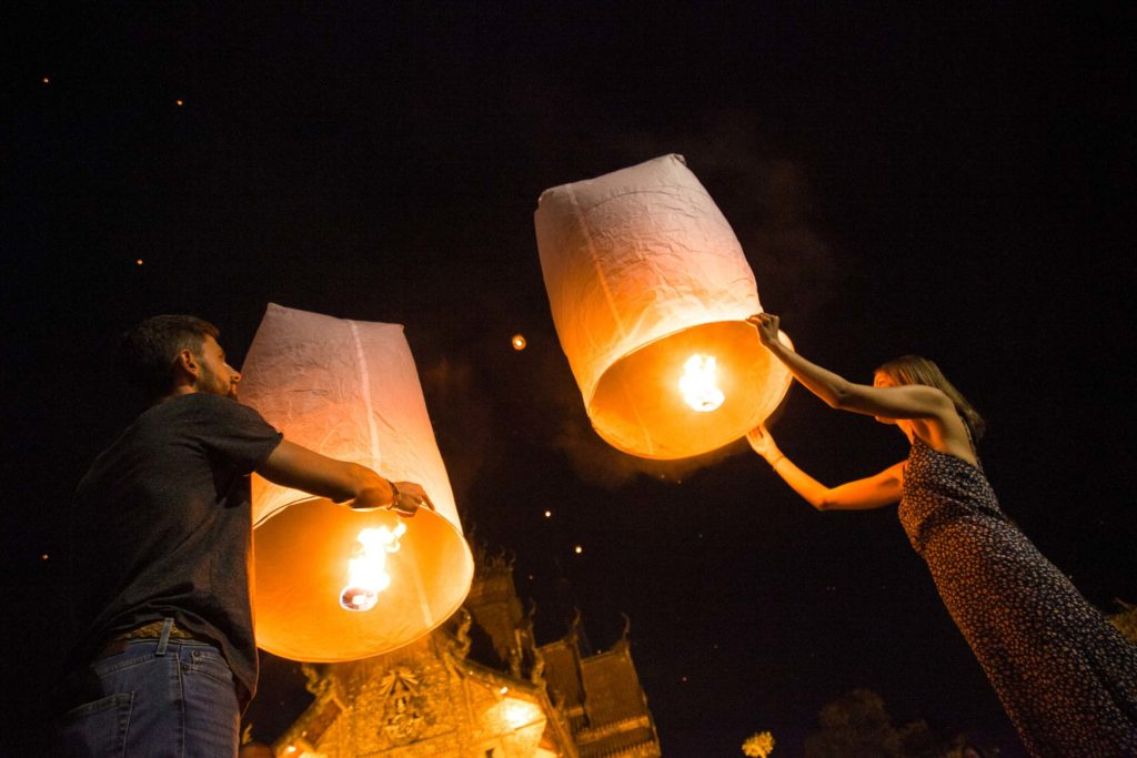 2 people releasing lanterns into the night sky during ye peng festival