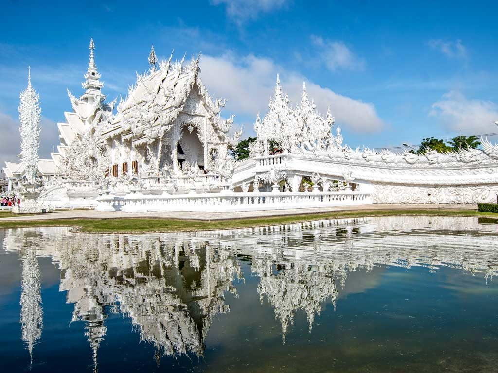 white impressive temple surrounded by water, was the best experiences in Thailand, Chiang Rai #thailand#thailandtravel#thailandtraveltips#thailandthingstodo#bestof thailandbucketlists#experiencesinthailand