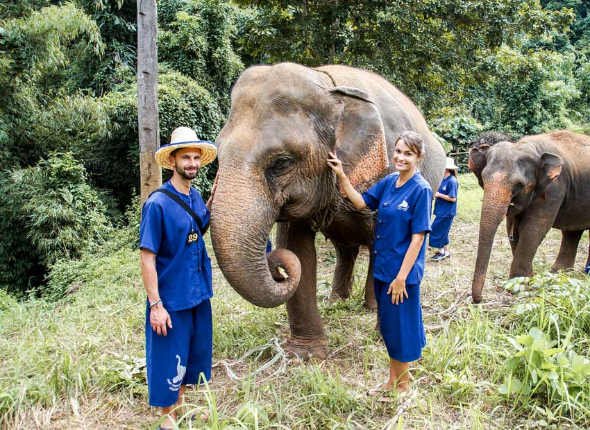 2 people in blue overals petting an elephant in an elephant sanctuary