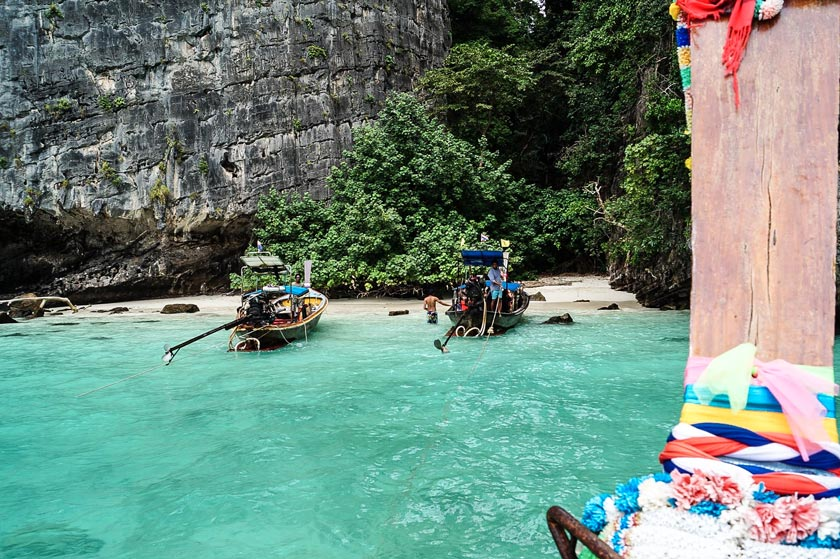 turquoise waters and boats at the shore, unique experiences in Thailand, Ko Phi Phi #thailand#thailandtravel#thailandtraveltips#thailandthingstodo#bestof thailandbucketlists#experiencesinthailand