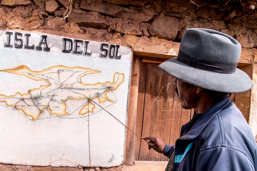 A man shows a map with sections of Isla del Sol