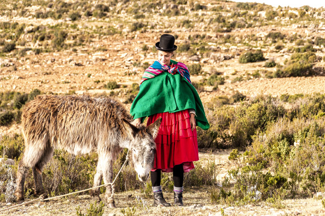 A woman pets a donkey