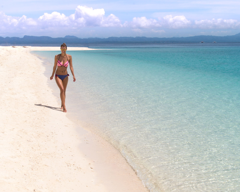 A girl walking on the white sand beach on Kalanggaman Island Philippines