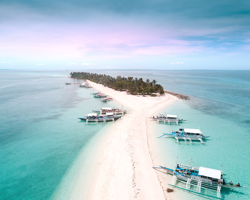 a view on the white sand island and palm trees, filipino boats which you need to add to your dreamy bucket list places