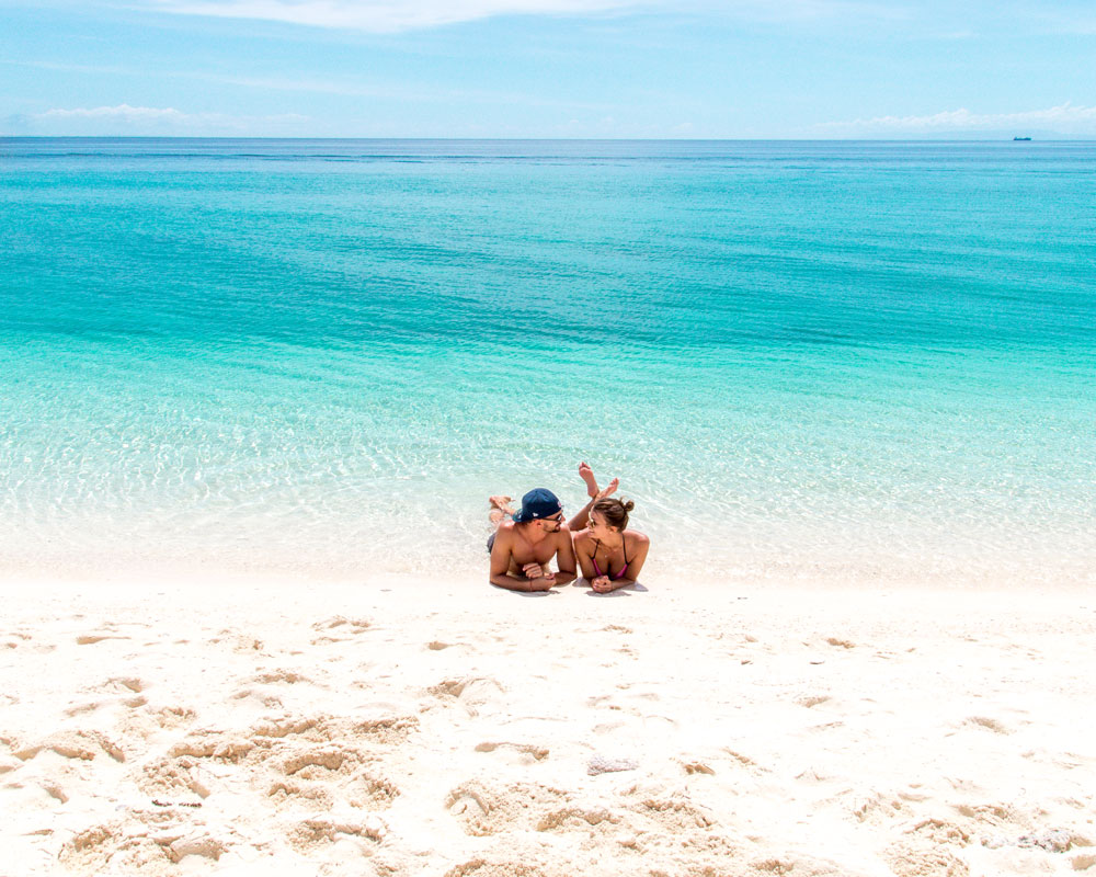two people sitting on the beach with white sand and blue waters
