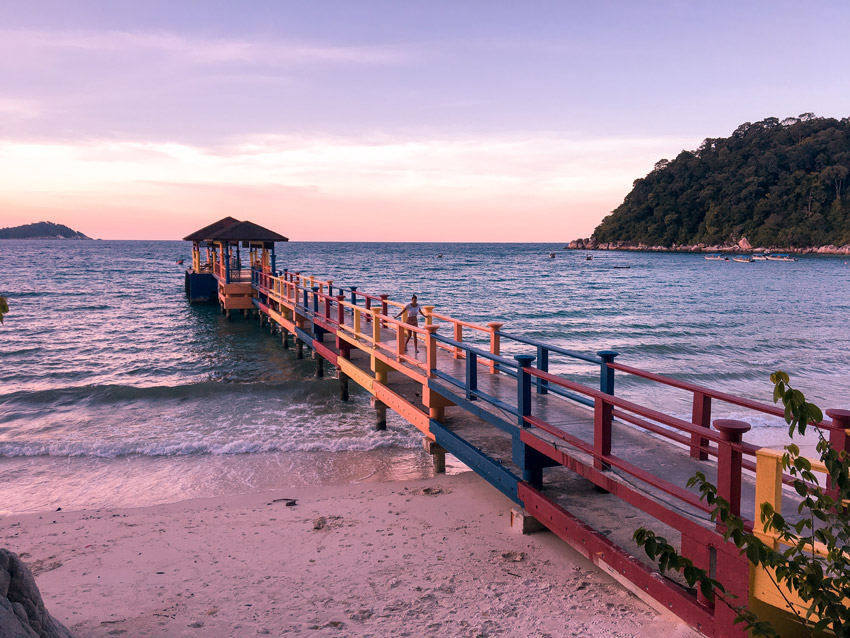 Sunset colors on a beach, a pier and the ocean.  How to get to perhentian islands