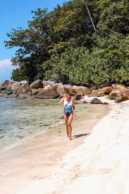 A girl walking on a beach. How to get to Perhentian islands.