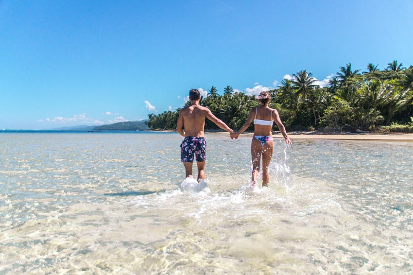 two people holding hands running in the water with green palm trees on Fiji