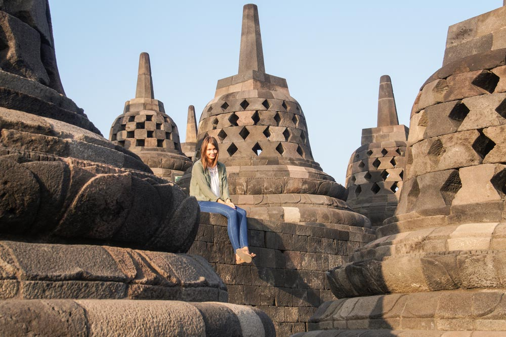 two weeks Indonesia itinerary Pretty girl sitting in front of stupas.