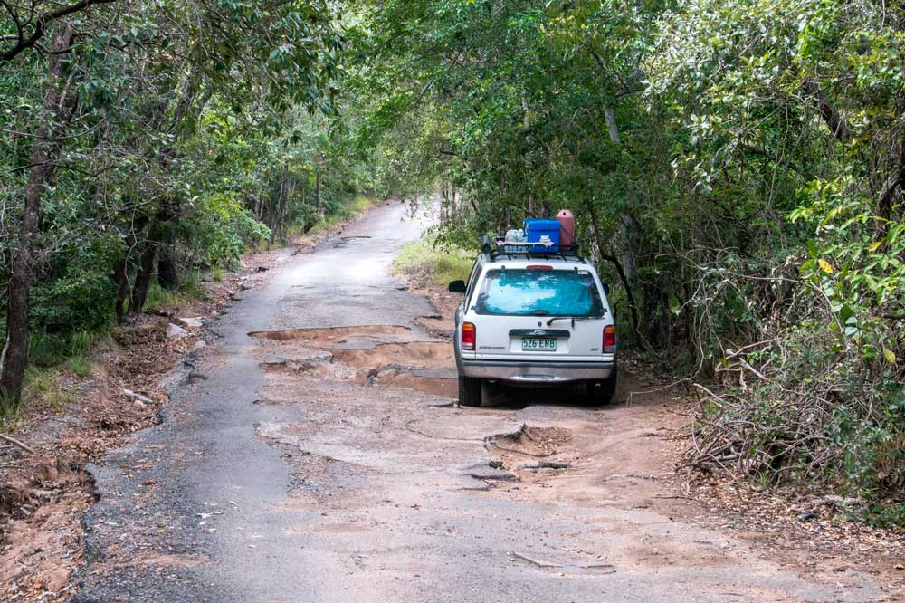 a 4WD driving on a street full of potholes on the way to radical bay on magnetic island